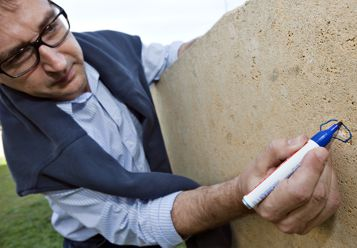A man with a felt pen circles a fossil on a stone.